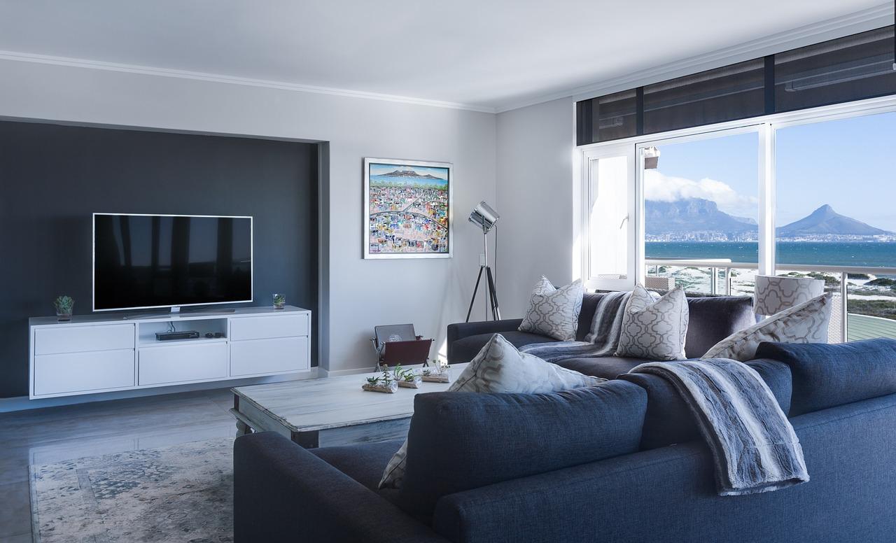 Soggiorno di una casa al mare con divano blu e vista sull'oceano